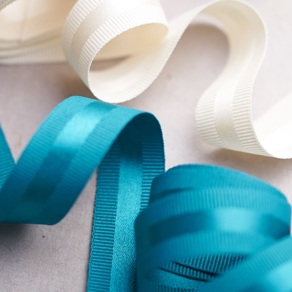 Home Impression Originale trio of ribbons white, black, teal on soft grey background