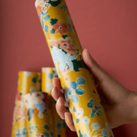 Home Impression Originale hand presenting gift rolls Behind the Frame on a terra cota background